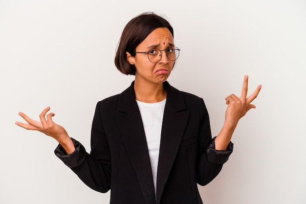 Young business indian woman isolated on white doubting and shrugging shoulders in questioning gesture.