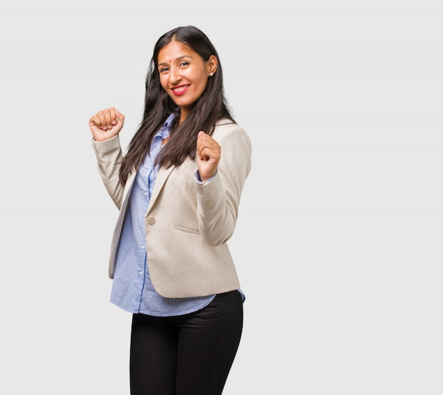 Young business indian woman listening to music, dancing and having fun, moving, shouting and expressing happiness, freedom concept