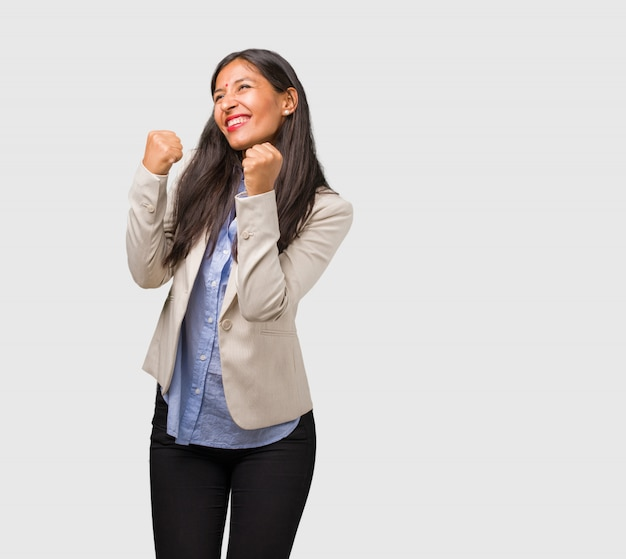 Young business indian woman very happy and excited, raising arms, celebrating a victory or success, winning the lottery