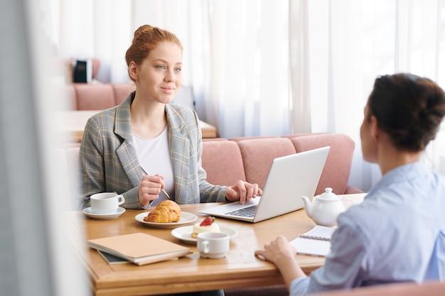 Молодые бизнес-леди в элегантных повседневных нарядах сидят за столиком в уютном ресторане и вместе планируют новый онлайн-проект