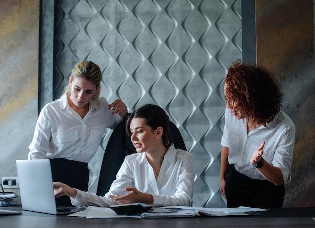 비즈니스 작업 사무실 집단 개념을 해결하는 동료와 함께 작동하는 랩톱 컴퓨터 작업 프로세스 비즈니스 회의를 사용하여 사무실 책상에 앉아 젊은 비즈니스 아가씨 여성 감독