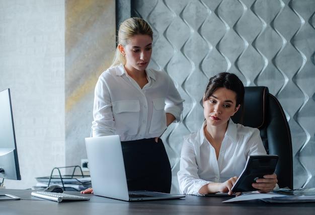 Direttore femminile della giovane signora di affari che si siede alla scrivania usando la calcolatrice che calcola la riunione d'affari di processo di lavoro che lavora con il concetto collettivo dell'ufficio di attività di affari di risoluzione del collega