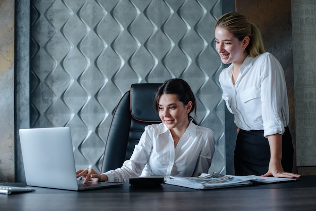 Young business lady female director sitting at office desk using laptop computer working process business meeting working with colleague solving business tasks office collective concept