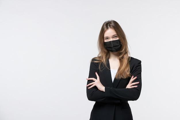 サージカルマスクを着用し、孤立した白い壁で誰かを注意深く聞いてスーツを着た若いビジネスレディ