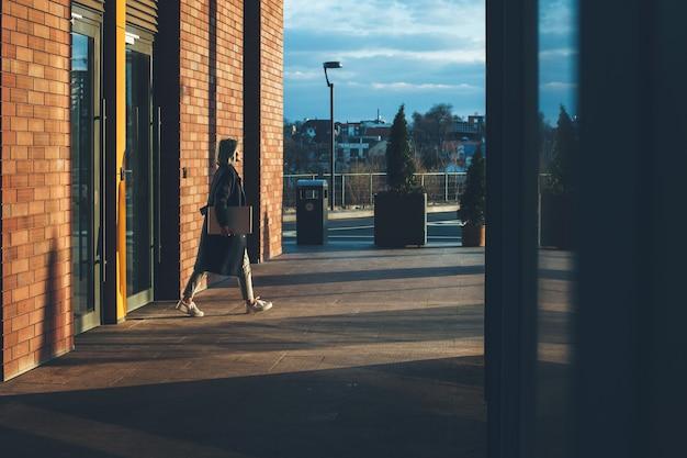 若いビジネスレディは、仕事の日を終えた後、ラップトップを持って外を歩いています
