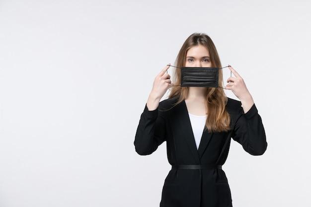 Giovane donna d'affari in tuta che rimuove la maschera medica dalla bocca sul muro bianco isolato