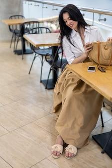공공 식당에서 원격으로 일하는 젊은 비즈니스 여성은 테이블에 앉아 스마트폰을 사용하여 채팅을 합니다.