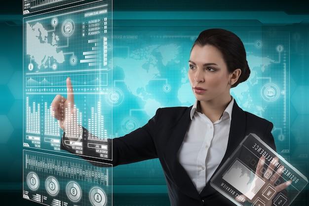 Молодая бизнес-леди работает с виртуальным графическим интерфейсом в футуристическом офисе