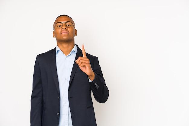 指でナンバーワンを示す白い壁に分離された若いビジネスラテン男。