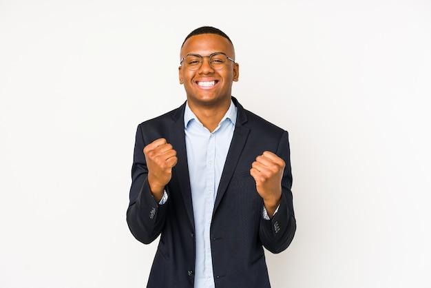 のんきと興奮して白い応援で孤立した若いビジネスラテン男。勝利のカバーセプト。