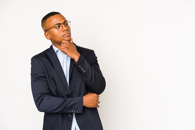 Young business latin man looking sideways with doubtful and skeptical expression.