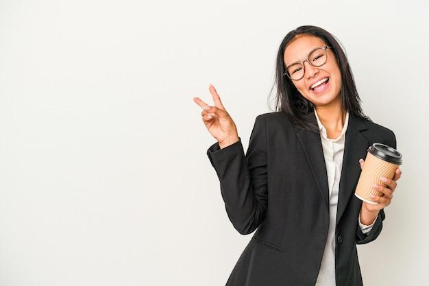 指で平和のシンボルを示す、楽しくてのんきな白い背景で隔離のテイクアウトコーヒーを保持している若いビジネスラテン女性。