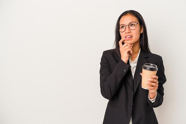 白い背景で隔離のテイクアウトコーヒーを保持している若いビジネスラテン女性は、コピースペースを見ている何かについて考えてリラックスしました。