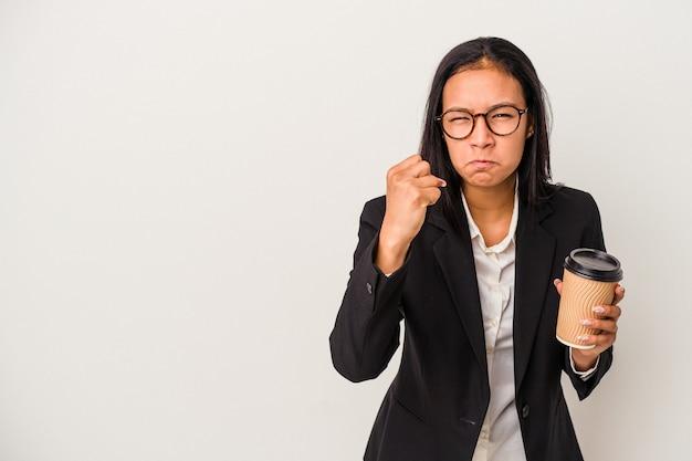 カメラに拳、積極的な表情を示す白い背景で隔離のテイクアウトコーヒーを保持している若いビジネスラテン女性。