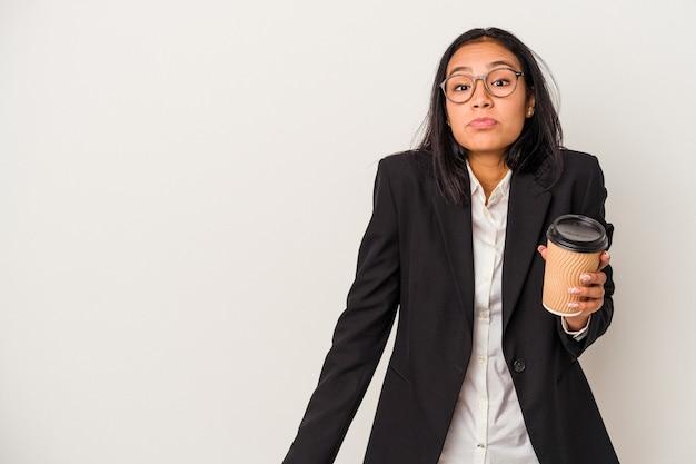 白い背景で隔離のテイクアウトコーヒーを保持している若いビジネスラテン女性は肩をすくめると混乱した目を開いています。