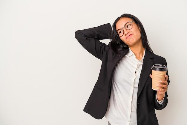 頭の後ろに触れて、考えて、選択をする白い背景で隔離のテイクアウトコーヒーを保持している若いビジネスラテン女性。