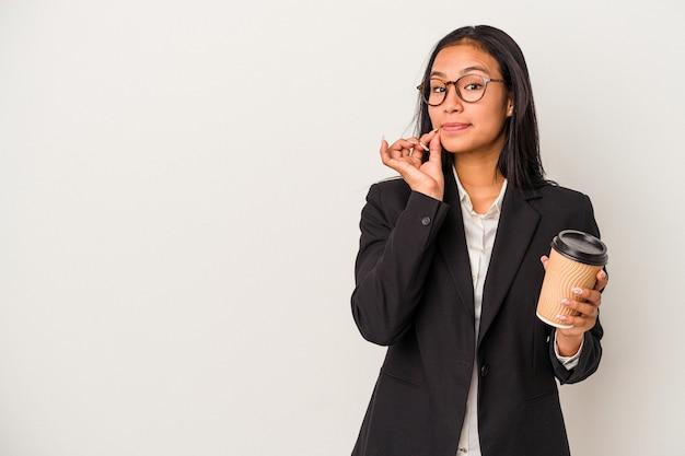 秘密を保持している唇に指で白い背景で隔離のテイクアウトコーヒーを保持している若いビジネスラテン女性。
