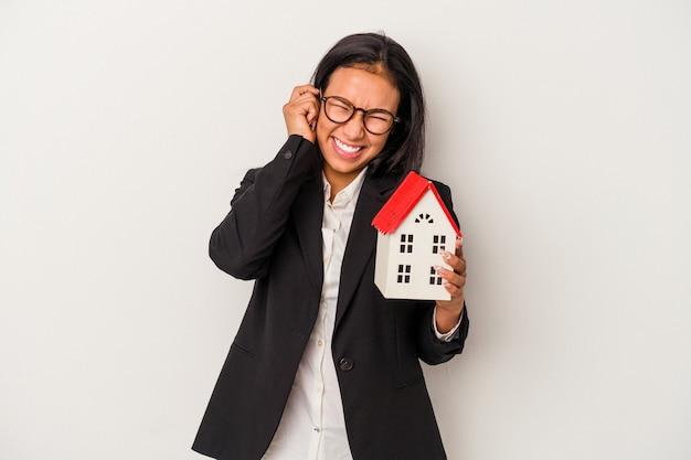 手で耳を覆う白い背景で隔離のおもちゃの家を保持している若いビジネスラテン女性。