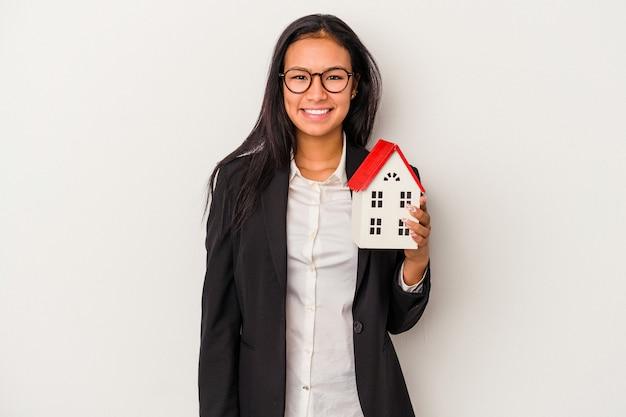 幸せ、笑顔、陽気な白い背景で隔離のおもちゃの家を保持している若いビジネスラテン女性。