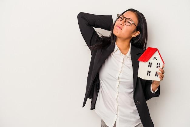 Молодой бизнес латинский женщина, держащая игрушечный домик на белом фоне, касаясь затылка, думая и делая выбор.
