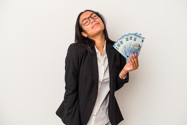 목표와 목적을 달성하는 꿈을 꾸고 흰색 배경에 고립 된 지폐 커피를 들고 젊은 비즈니스 라틴 여자