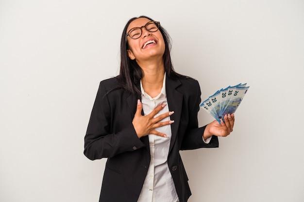 白い背景で隔離の手形コーヒーを保持している若いビジネスラテン女性は、胸に手を置いて大声で笑います。