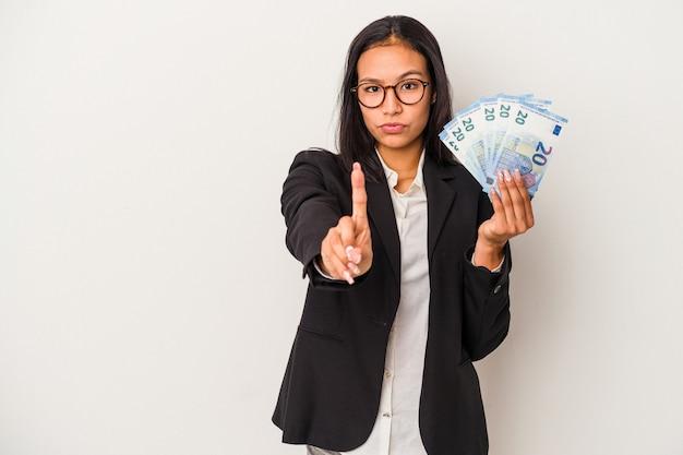 흰색 배경에 격리된 지폐를 들고 있는 젊은 비즈니스 라틴 여성은 손가락으로 1번을 보여줍니다.