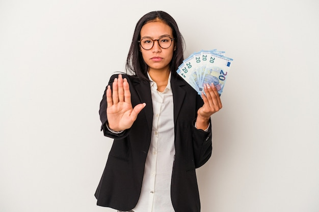 一時停止の標識を示す伸ばした手で立っている白い背景で隔離の手形コーヒーを保持している若いビジネスラテン女性は、あなたを防ぎます。