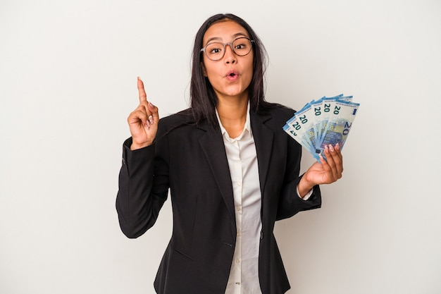 Young business latin woman holding bills coffee isolated on white background  having an idea, inspiration concept.