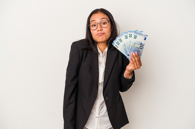 Young business latin woman holding bills coffee isolated on white background  shrugs shoulders and open eyes confused.