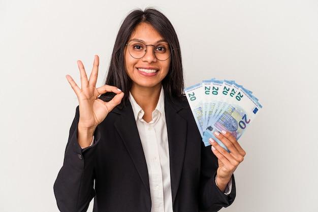 白い背景に分離された手形を保持している若いビジネスラテン女性は、明るく自信を持って大丈夫なジェスチャーを示しています。