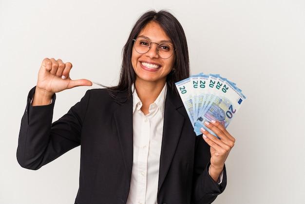 흰색 배경에 격리된 지폐를 들고 있는 젊은 비즈니스 라틴 여성은 자부심과 자신감을 느낍니다.