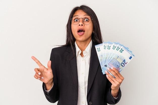 측면을 가리키는 흰색 배경에 고립 된 지폐를 들고 젊은 비즈니스 라틴 여자