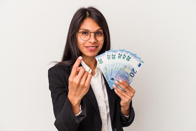 흰색 배경에 격리된 지폐를 들고 있는 젊은 비즈니스 라틴 여성은 마치 초대하는 것처럼 손가락으로 당신을 가리키고 있습니다.