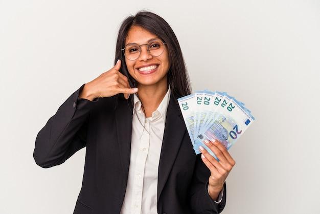 指で携帯電話の呼び出しジェスチャーを示す白い背景で隔離の請求書を保持している若いビジネスラテン女性。