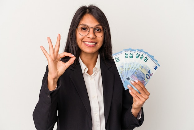 Young business latin woman holding bills isolated on white background cheerful and confident showing ok gesture.
