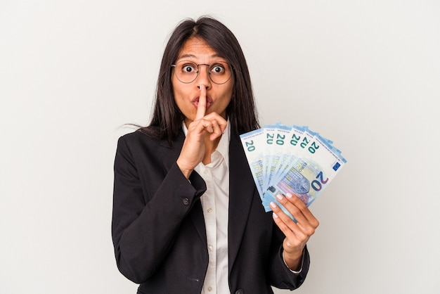 Young business latin woman holding bills isolated on white background keeping a secret or asking for silence.