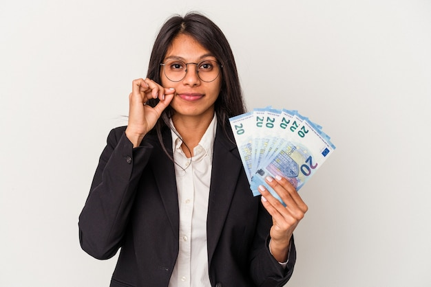 Young business latin woman holding bills isolated on white background with fingers on lips keeping a secret.