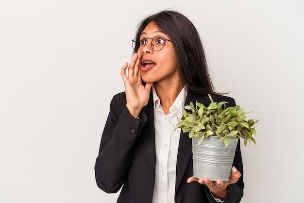 白い背景で隔離の植物を保持している若いビジネスラテン女性は秘密のホットブレーキニュースを言って脇を見ています