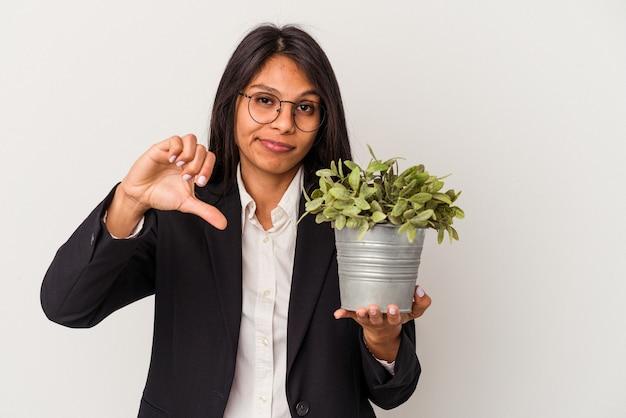 嫌いなジェスチャーを示す白い背景で隔離の植物を保持している若いビジネスラテン女性、親指を下に。不一致の概念。