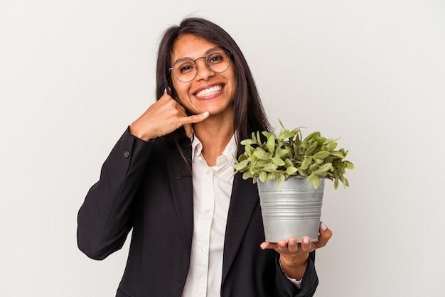 指で携帯電話の呼び出しジェスチャーを示す白い背景で隔離の植物を保持している若いビジネスラテン女性。
