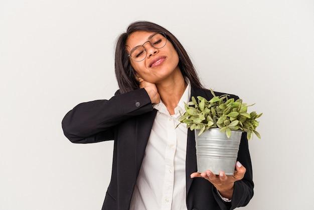 머리 뒤를 만지고 생각하고 선택하는 흰색 배경에 고립 된 식물을 들고 젊은 비즈니스 라틴 여자.