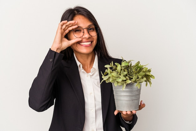 Young business latin woman holding plants isolated on white background excited keeping ok gesture on eye.