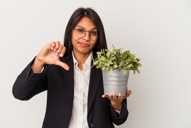 Young business latin woman holding plants isolated on white background showing a dislike gesture, thumbs down. disagreement concept.