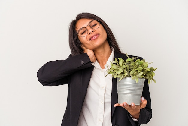 Young business latin woman holding plants isolated on white background touching back of head, thinking and making a choice.