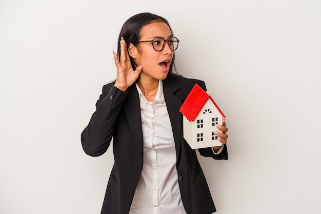 Young business latin woman holding a toy house isolated on white background  trying to listening a gossip.