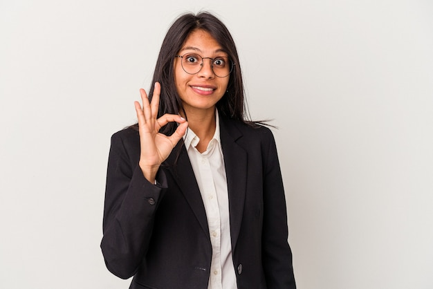 흰색 배경에 격리된 젊은 비즈니스 라틴 여성은 쾌활하고 자신감 있는 확인 제스처를 보여줍니다.