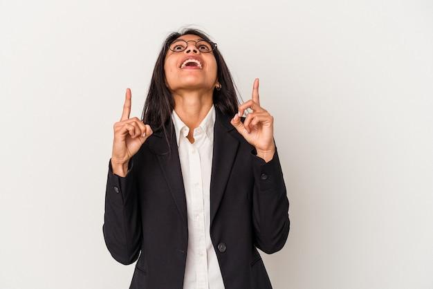 口を開けて逆さまを指している白い背景で隔離の若いビジネスラテン女性。