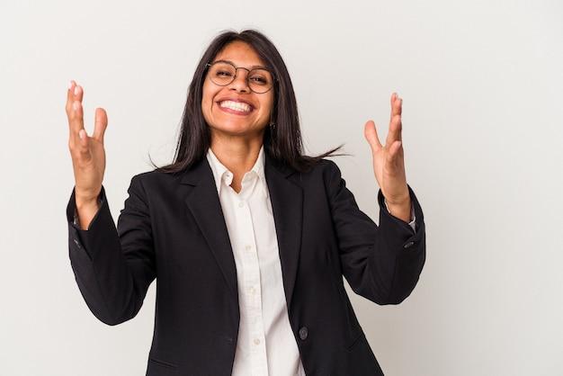 嬉しい驚きを受け取り、興奮し、手を上げる白い背景で隔離の若いビジネスラテン女性。