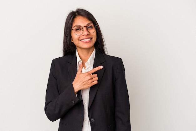 흰색 배경에 격리된 젊은 비즈니스 라틴 여성은 웃고 옆으로 가리키며 빈 공간에서 뭔가를 보여줍니다.
